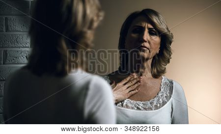 Sad Senior Female Looking In Mirror With Disgust, Aging Problem, Insecurities