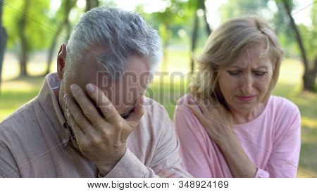 Mature Couple Crying Sitting Outdoors, Incurable Disease, Retirement Problem