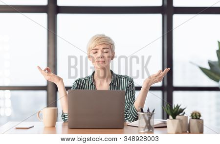 Mature Businesswoman Meditating Relaxing At Workplace Sitting In Modern Office. Meditation And Work
