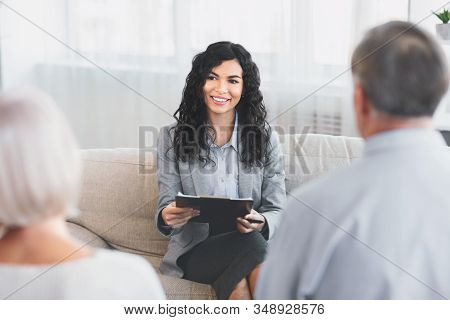Savings Plan. Senior Couple Meeting With Mexican Financial Advisor At Home, Discussing Their Mortgag