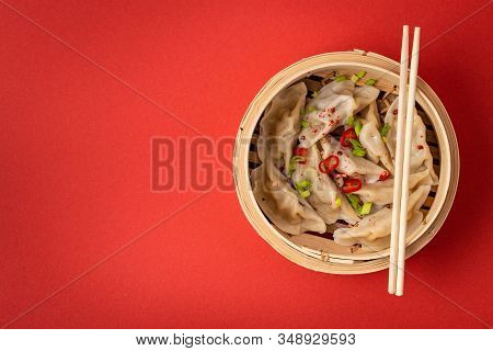 Traditional Chinese Steamed Dumplings In Bamboo Steamer With Wooden Chopsticks On Red Background, Cl