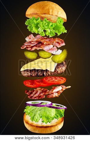 Hamburger With Flying Ingredients Isolated On A Dark Background. High Resolution Image. Flying Ingre
