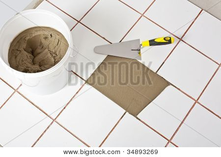 Trowel And Old White Tiles With Tile Adhesive