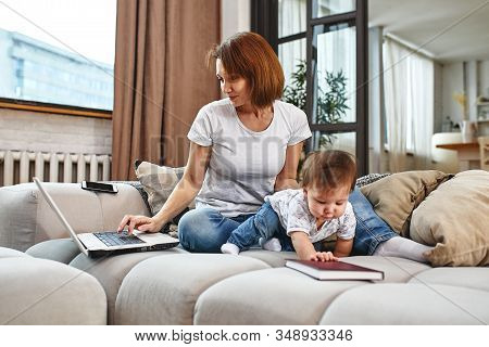 A Woman With A Child At A Laptop Sitting On A Sofa. Work At Home, Freelancer, Work During Maternity