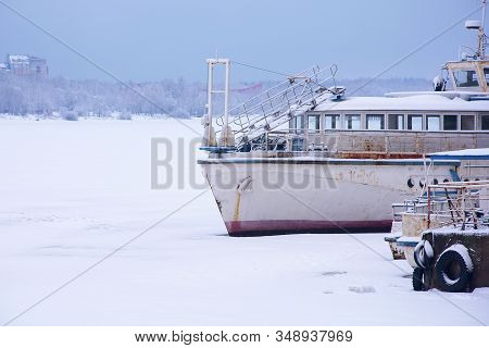 Old Rusty Ship In The Winter At The Pier. Frozen River. Soft Focus.