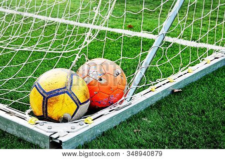Two Ragged Shabby Soccer Balls Lying In The Corner Of The Goal. Everybody Loves To Play Football. Th