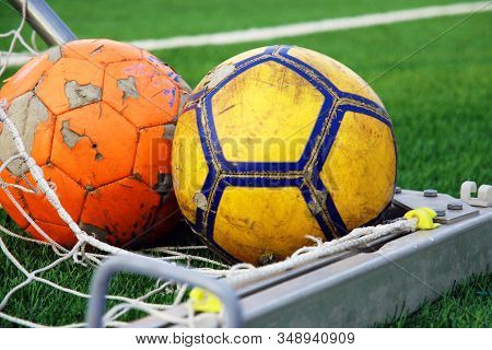 Two Ragged Soccer Balls Lying In The Corner Of The Goal Against Green Football Field, Close-up