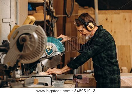 Side View Of Craftsperson Using Circular Saw Over Wooden Plank At Workshop