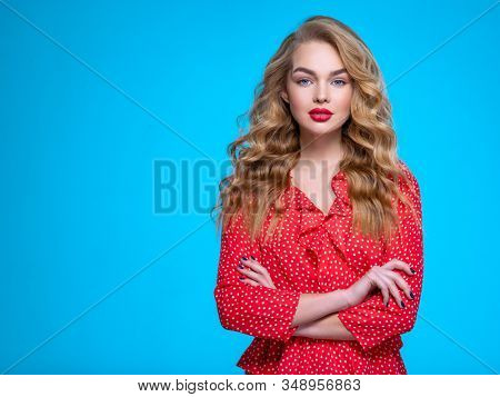 Portrait of a calm young blonde. Beautiful girl with long white hair. Model in a red shirt poses in studio. People with crossed arms.  Caucasian woman with a tranquil emotions. Calmness concept.