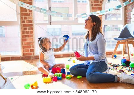 Caucasian girl kid playing and learning at playschool with female teacher. Mother and daughter at playroom around toys playing with bulding blocks