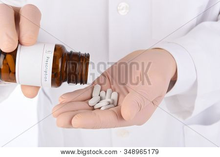 Closeup of a doctor pouring pills into his gloved hand. Man is unrecognizable.
