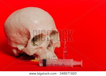 Human Skull On A Red Background With An Ampule And A Syringe With A Vaccine. The Concept Of Death Fr