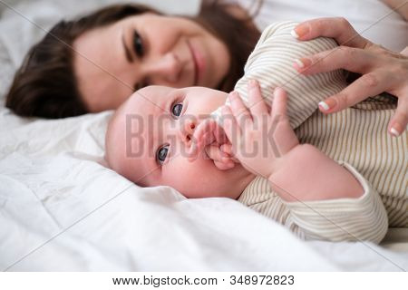 Mother Love. Caucasian Young Brunette Woman Mom Looking To Her Little Cutest Baby Lying In Bed. Infa