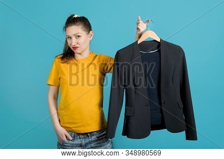 A Girl In Bright Clothes Holds A Hanger With A Business Suit And Shows Her Dislike. Blue Background