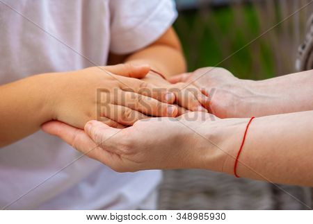 close up hands of grandson and grandmother