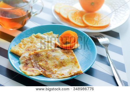 Crepe-suzette Pancakes In Orange-cream Sauce. The Concept Of Holiday Carnival