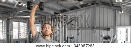 Gym workout fitness banner panoramic man training with dumbbells lifting overhead raise shoulders exercise shoulder press indoors.