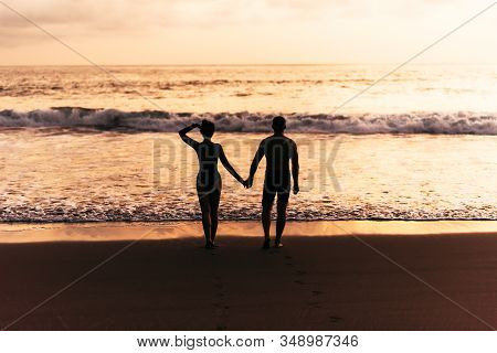 Silhouette Of Loving Couple On Sea. A Couple In Love At Sunset. Man And Woman Meet Sunset. Happy Lov