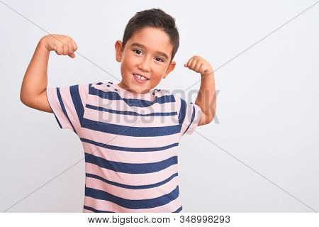 Beautiful kid boy wearing casual striped t-shirt standing over isolated white background showing arms muscles smiling proud. Fitness concept.