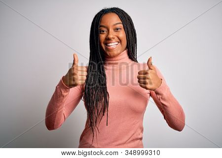 Young african american woman standing casual and cool over white isolated background success sign doing positive gesture with hand, thumbs up smiling and happy. Cheerful expression and winner gesture.