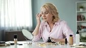 Blond female in her 50s looking attentively in mirror, anti-wrinkle cosmetics poster
