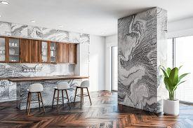 Corner Of Luxury Kitchen With Gray Marble Walls, Wooden Floor, Marble Countertops, Wooden Cupboards