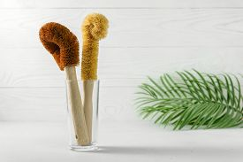 Two Scrapers Made Of Coconut Bristles And A Bamboo Handle In A Glass Cup. Biodegradable Kitchen Acce