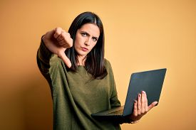 Young brunette woman with blue eyes working using computer laptop over yellow background looking unhappy and angry showing rejection and negative with thumbs down gesture. Bad expression.