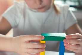 Little Blond Girl Playing Board Games. Board Games Concept. Wooden Builing Blocks In Girls Hands. Ki