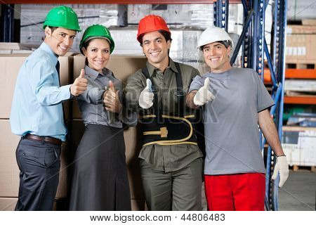 Portrait of happy foremen and supervisors gesturing thumbs up at warehouse - shallow depth of field, focus on thumbs