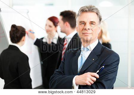 Business - Team in einem Büro, der leitenden Angestellten steht im Vordergrund