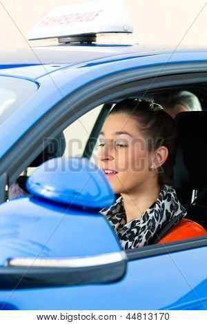 Driving School - Young woman steer a car, maybe she has a driving test and the driving examiner sits on the back seats