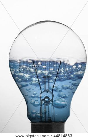 Light bulb and blue water inside against white background