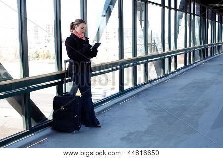 Pretty Blond Business Woman Using A Tablet Computer While Traveling With Her Rolling Luggage At The Airport