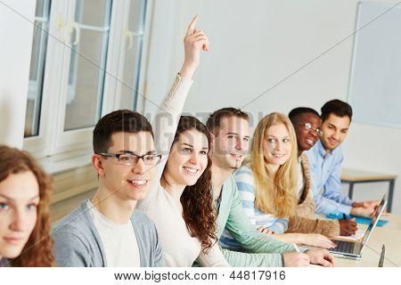 Young smiling woman raising her hand in a university class