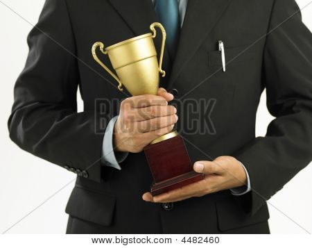A Winner With Suit Holding A Trophy