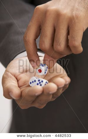 Close Up Of Man Picking Up A Dice