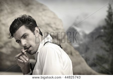 Sexy hunky male model outdoors smoking cigar with seductive look and vintage feel