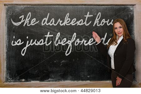 Teacher Showing The Darkest Hour Is Just Before Dawn On Blackboard