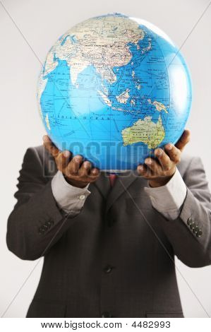 Man Holding Globe Over Face