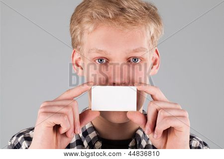 Portrait of young handsome guy holding a blank card over grey background