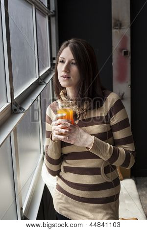 Beautiful Young Woman With Brown Hair Drinking Glass Of Mango Juice