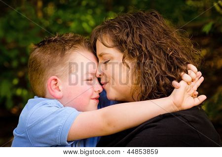 Mother and son hugging with woman kissing child