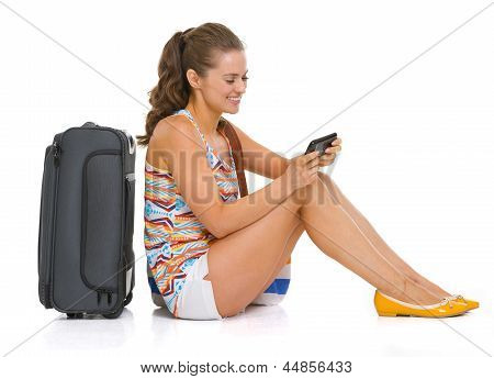 Young Tourist Woman With Wheel Bag Sitting On Floor And Writing