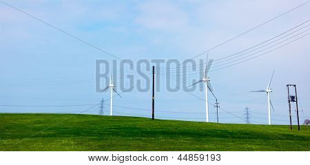 Wind turbines over a green hill