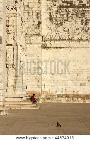Father with little daughter sitting on the doorstep of the catholic cathedral in Lisbon, Portugal