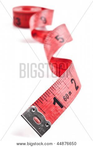 Red tape measure on rolled up on white background