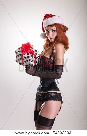 Pinup girl in Santa Claus hat, holding gift box, Christmas theme