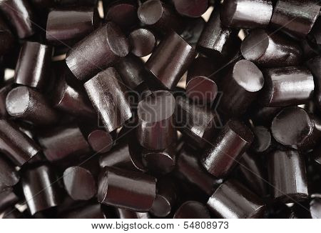 black pieces liquorice candy background, close up poster