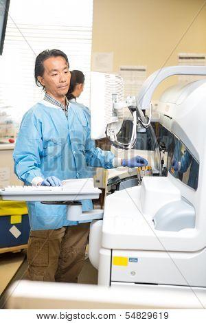 Lab tech loading specimen in chemical analyzer